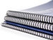 stack of spiral-bound workbooks