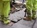 two sidewalk workers in bright green pants digging up concrete pavement