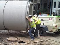 Design Build Manual Thumbnail - Workers Moving Large Sewer pipe