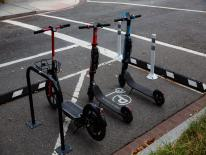 Three Dockless Scooters in an off sidewalk micro mobility corral