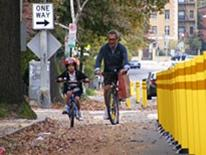 Bicycle Program - an adult riding a bike alongside a child on a training-bike in a bike lane