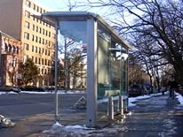 DC Bus Shelter Program - DC bus shelter in front of an apartnent building with melting snow on the nearby ground
