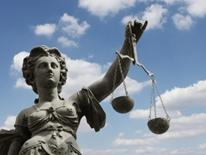 Civil Rights image of classic Greek female sculpture holding the scales of justice in front of a blue, clouded sky