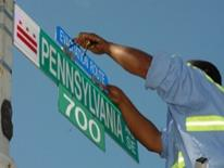 Emergency Preparedness - DDOT worker installing a special emergency evacuation route placard to a street sign