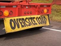 Permits and Tags for Oversize and Overweight Vehicle Operation - yellow and black text oversize load banner on back of red truckm