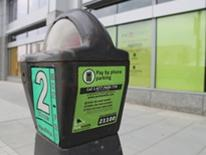 Pay by Phone single headed parking meter with bright green instructions sticker on the side