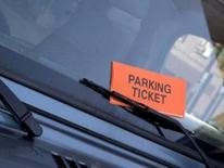 Parking Enforcement and Adjudication - orange parking ticket envelope placed under wiper blade on auto windshield