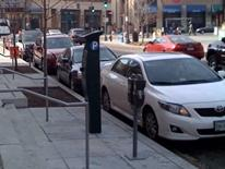 Performance Based Parking Pilots - several cars parked alongside a city sidewalk with meters