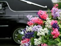 Reserve Parking for a Funeral - herse with a funerary floaral arrangement in the foreground