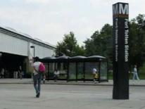 South Dakota Avenue Transportation and Streetscape Study - Fort Totten Metro Station bus shelter area with sign and person walking