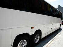 Tour Bus Parking - side view of white tour bus from back to front