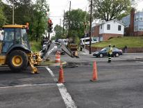 a street repair crew working in an intersection with traffic cones and equipment