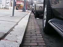 photo of a granite curb and brick-lined gutter on District street