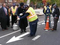 Photo of DDOT worker showing people how to spray pavement marking arrow