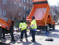 Street Repair - a DDOT crew working next to an orange dump truck and an orange asphalt depositor repairing a city street