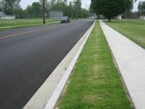 photo of a newly repaved street, a new sidewalk, and newly planted grass