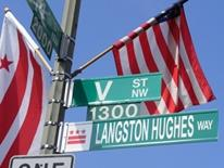 Street Signs - a light pole with several green and white steet name signs, an American flag, and a DC flag