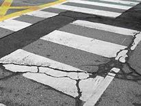 Photo of badly cracked painted street crossing area of a city roadway needing utilities cut off prior to repairs