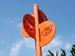 Carshare Initiative - 4-way orange-colored sculptural carshare signs on post