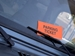 Parking Enforcement and Adjudication - orange parking violation ticket on windshield, under wiper blade